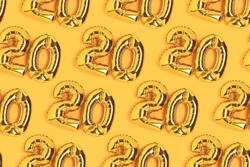 Numbers 20 golden balloons pattern. Twenty years anniversary celebration layout on a yellow background.