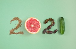 numbers 2021 made from fruits and vegetables on green background , Healthy happy New year , diet goals and lifestyle
