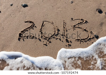 Numbers 2013 on sea beach sand with tide wave water