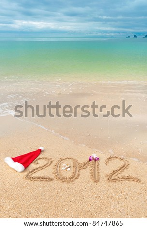 Numbers 2012 on tropical beach sand - vertical holiday background