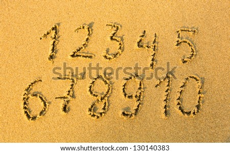 Numbers one to ten written on a sandy beach.