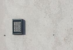 numeric keypad on concrete wall
