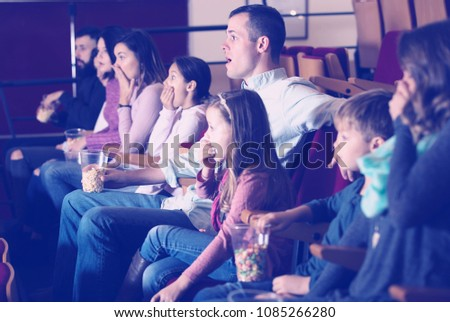 Numerous audience eating popcorn and fun to watch a movie at the cinema #1085266280