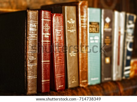 Numerous Holy Bibles sit in a row on an antique wood shelf.  The well-used bibles are various translations, versions, and ages.  Shallow depth of field, with focus point on the far left bibles.