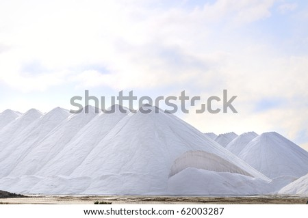 Numerous large piles of white salt at a salt works.