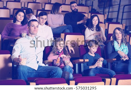 Numerous spectators eating popcorn and enjoy watching movie in the cinema