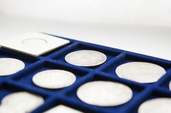 Numismatic collection coin pile on blue tray isolated white background