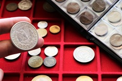 Numismatic job. World coins collection, investment. Accessories are visible in the background.