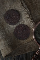 Numismatics. Old collectible coins and a magnifying glass on a wooden table. Dark background. Top view.
