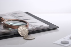 Numismatics. Old collectible coins and a magnifying glass on the table. Light background.