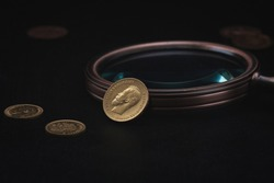 Numismatics. Old collectible coins made of gold on a wooden table.  Dark background.