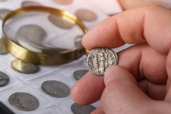 Numismatics. Old collectible coins made of silver on a wooden table. A collector holds an old coin.Ancient coin of the Roman Empire.