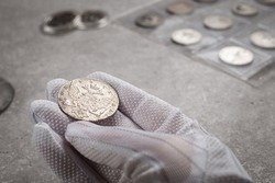 Numismatics. Old collectible coins made of silver on a wooden table. A collector in special gloves holds an old coin.