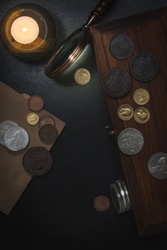 Numismatics. Old collectible coins of silver, gold and copper on the table.  A collector in special gloves holds an old coin. Top view.