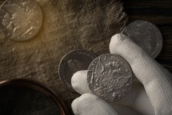 Numismatics. Old collectible coins of silver on the table.  A collector in special gloves holds an old coin. Top view.