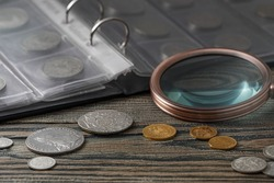 Numismatics. Old collectible coins on a wooden table.  Dark background.