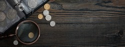 Numismatics. Old collectible coins on a wooden table.  Dark background. Banner.  Copy space of your text.