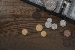 Numismatics. Old collectible coins on a wooden table.  Dark background. Top view.