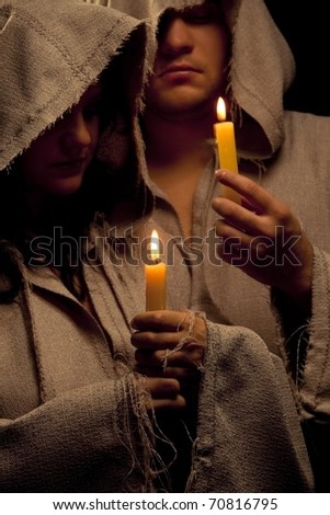 Nun and monk praing with candles in their hands