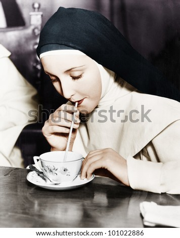 Nun sipping tea out of a teacup with a straw