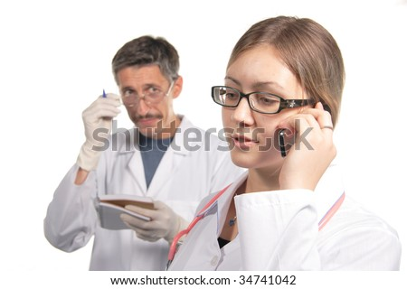 nurse accepts a telephone call. On a background there is a doctor.