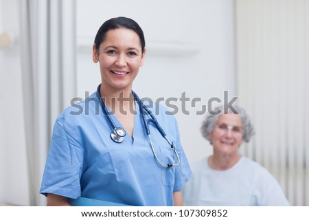 Nurse and a patient looking at camera in hospital ward