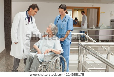 Nurse and doctor talking with old woman sitting in wheelchair in hospital corridor