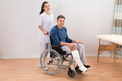Nurse Assisting Disabled Patient Sitting On Wheelchair