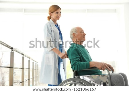 Nurse assisting elderly man in wheelchair indoors