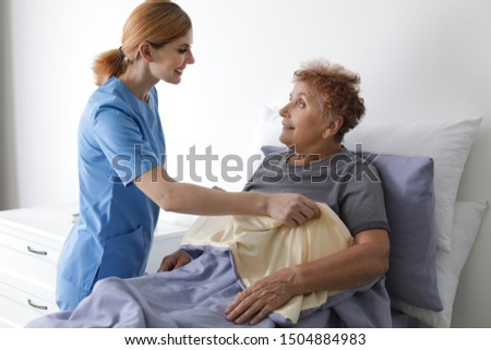 Nurse assisting elderly woman in bed indoors