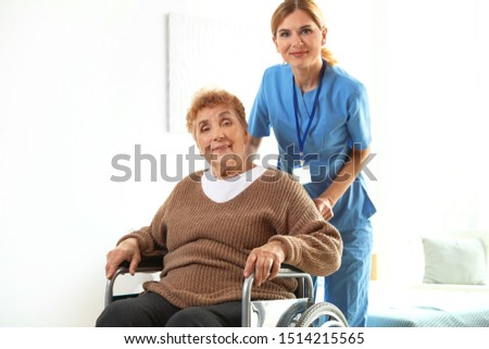 Nurse assisting elderly woman in wheelchair indoors