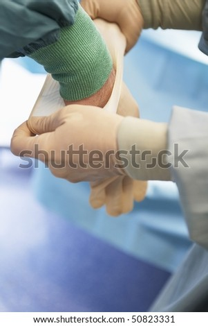 Nurse assisting surgeon Putting on Sterile Latex Gloves, close up of hands
