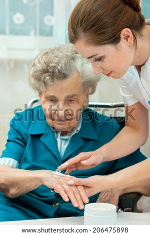 Nurse assists an elderly woman with skin care and hygiene measures at home