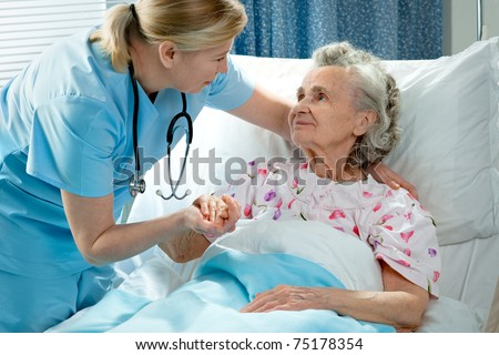 Nurse cares for a elderly woman lying in bed
