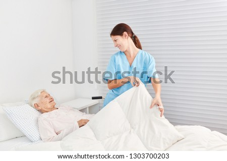 Nurse cares for a sick senior citizen in bed in nursing home or hospice