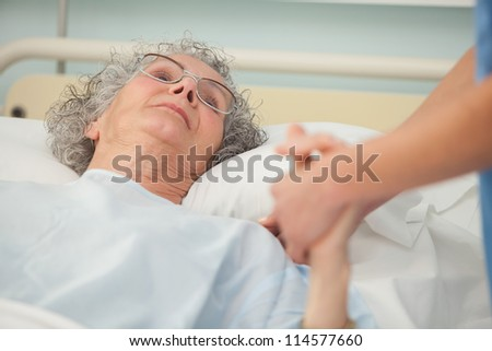 Nurse caring about old woman lying in bed - stock photo