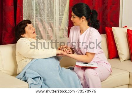 Nurse comforting sick elderly woman in her home