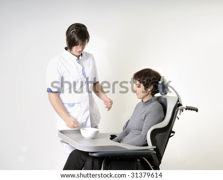 nurse feeding an adult disabled woman in wheelchair