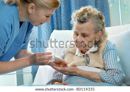 nurse gives a senior woman the medicine