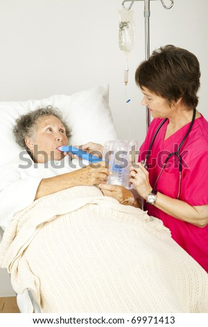 Nurse gives respiratory therapy to a patient recovering in the hospital.