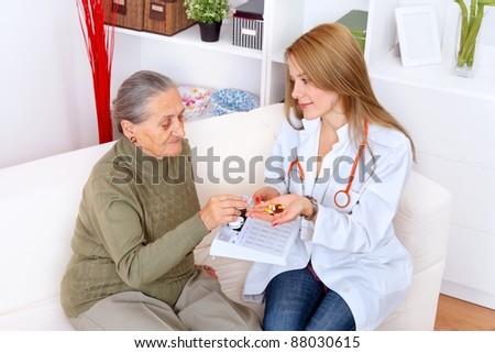 Nurse gives the senior woman her medicines