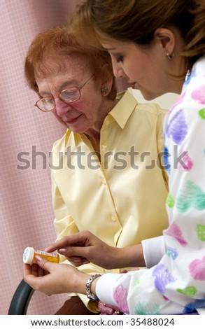 nurse giving senior woman pills