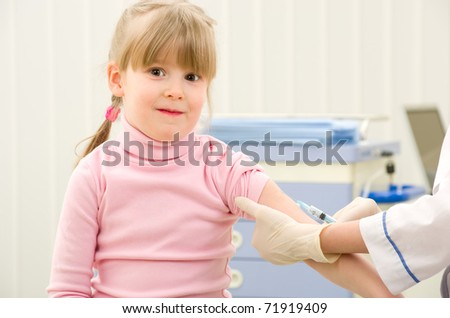 Nurse giving vaccination to little girl by syringe in hand
