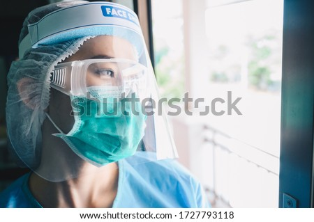 Nurse having tired from work while wearing PPE suit for protect coronavirus disease. PPE while protecting healthcare workers from exposure to the COVID-19 virus in healthcare settings.