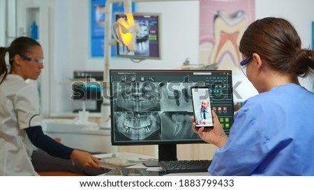 Nurse having video call with expert stomatologic medic while doctor is working with patient in background. Stomatologist assistant listening dentist using mobile webcam sitting on stomatological chair Photo stock ©