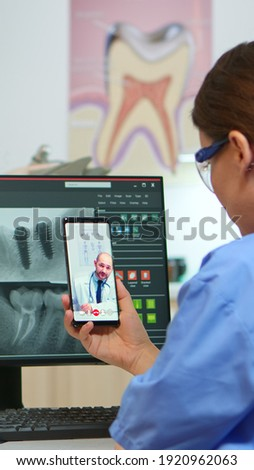 Nurse having video call with expert stomatologic medic while doctor is working with patient in background. Stomatologist assistant listening dentist using mobile webcam sitting on stomatological chair Foto stock ©