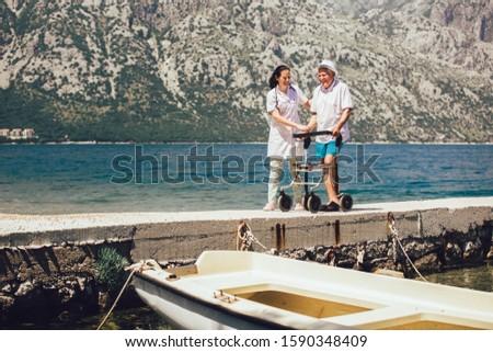 Nurse helping elderly senior man. Senior man using a walker with caregiver near the sea at summer.