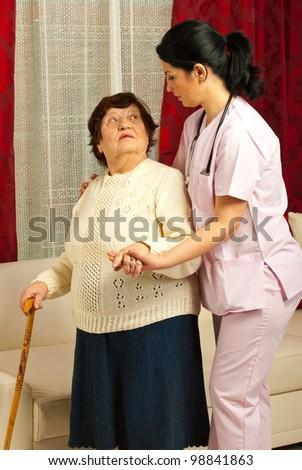 Nurse helping elderly woman to walk in her home