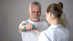 Nurse helping old man to lift dumbbell, cardiac rehabilitation, injury recovery