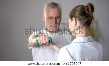 Nurse helping old man to lift dumbbell, cardiac rehabilitation, injury recovery #1461703247